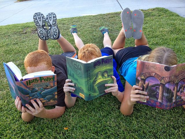 Three children lying on grass, reading