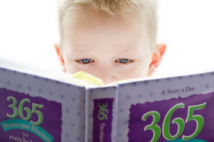 Young boy reading book, close up