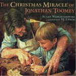 This is the cover of the picture book THE CHRISTMAS MIRACLE OF JONATHAN TOOMEY. A woodcarver in an apron is helping a young boy carve one of the figures for a Nativity scene.