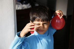 boy in blue with red balloons