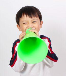 Asian boy shouting into green meaphone