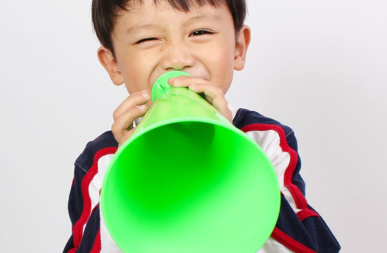 Asian boy shouting into green meaphone