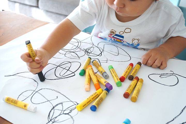 Small child scribbling with what looks like oil pastel crayons